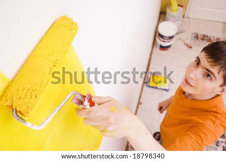 Young man painting the walls in a new house - stock photo
