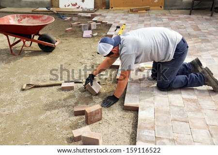 Young man paving or laying down paver as part of landscaping - stock photo