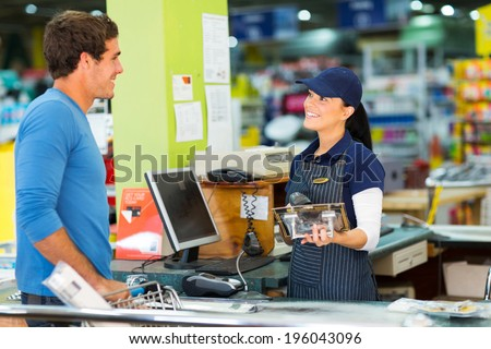 young man paying at till point in hardware store - stock photo
