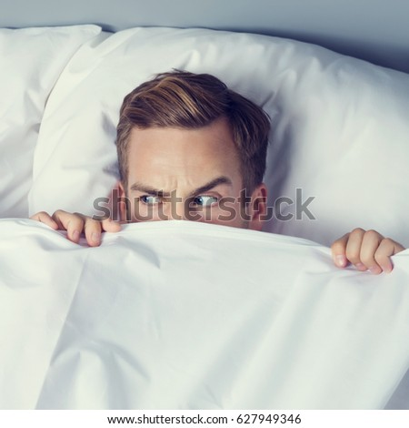 Young man peeping from bedsheet on the bed at bedroom  Caucasian model in  happy people. Peeping From Bedsheet Stock Images  Royalty Free Images   Vectors