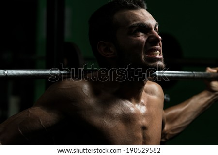 Young Man Performing Barbell Squats - One Of The Best Body Building Exercise For Legs - stock photo