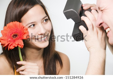 young man photographed his with a polaroid camera his girlfriend with flower  - stock photo