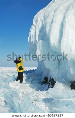 Young man photographer getting picture of ice cornice on the rock. The Baikal Lake