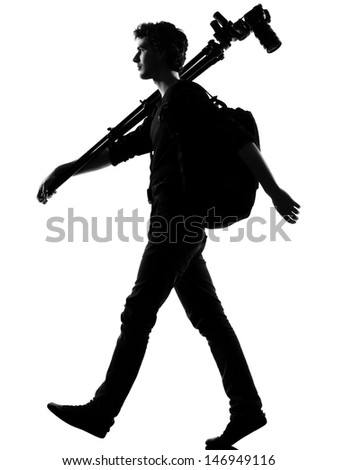 young man photographer silhouette in studio isolated on white background - stock photo