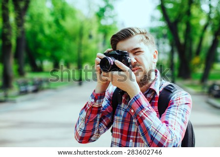 Young man photographer with a beard taking photos on old film camera outdoors in the alley, in the park, close-up  - stock photo
