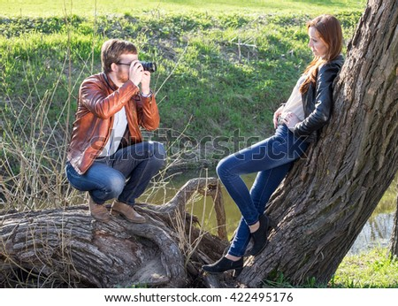 Young man photographing attractive girlfriend in park in sunny day - stock photo