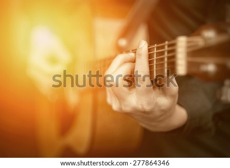 Young man play on the acoustic guitar - stock photo