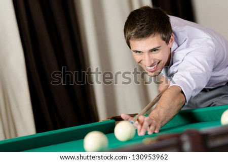 Young man playing billiard. Spending free time on gambling - stock photo