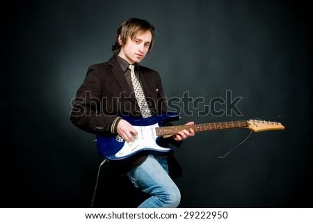 Young man playing electro guitar, studio shot - stock photo