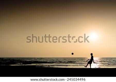 Young man playing football silhouette ocean horizon sunset horizontal illustration - stock photo