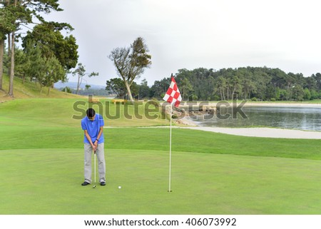 Young man playing golf - stock photo