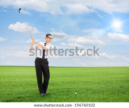 Young man playing golf on a field isolated on white background shot with tilt and shift lens