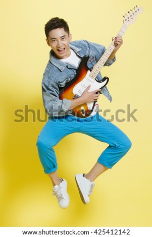 Young man playing guitar - stock photo