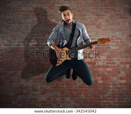 Young man playing guitar on brick wall background - stock photo