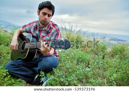 Young man playing guitar outside