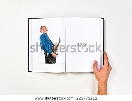 Young man playing guitar printed on book - stock photo