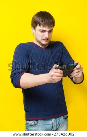 young man playing on a tablet - stock photo