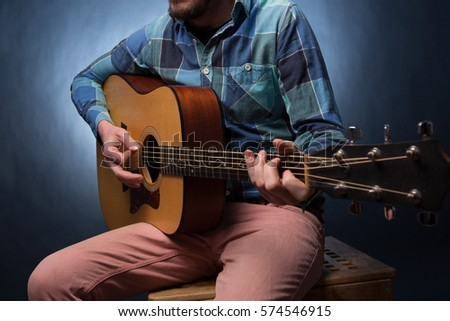 Young Man Playing On Acoustic Guitar Close Up Dark Blue Background