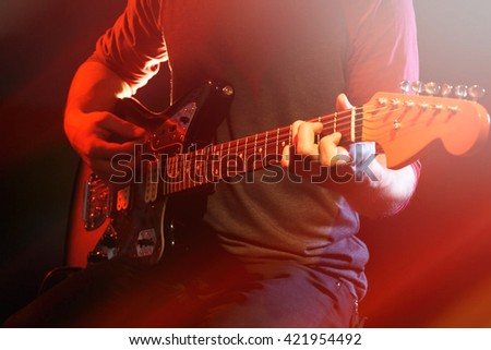 Young man playing on electric guitar on dark background with light effect