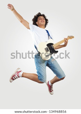 young man playing on electro guitar and jumping - stock photo