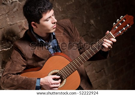 Young man playing on guitar. Camera angle view. - stock photo