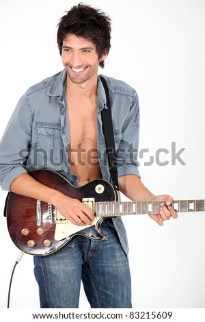 young man playing on his electric guitar - stock photo