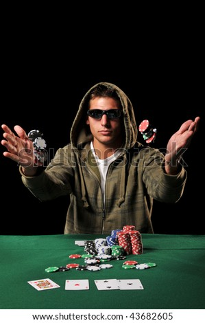 Young man playing poker tossing chips against a black background - stock photo