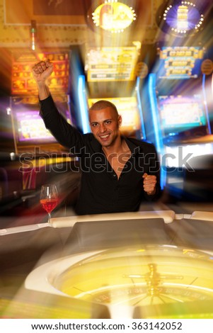 Young man playing roulette in casino betting and winning