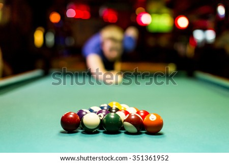 Young man playing snooker in the bar - stock photo