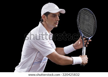 Young man playing tennis isolated over black background