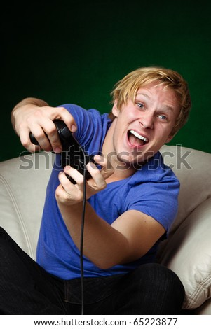 young man playing video games on dark green background
