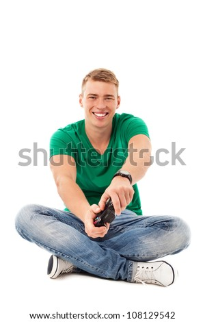 Young man playing video games, sitting on floor isolated on white background - stock photo