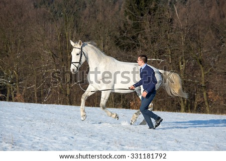 Young man playing with her horse in the snow - stock photo