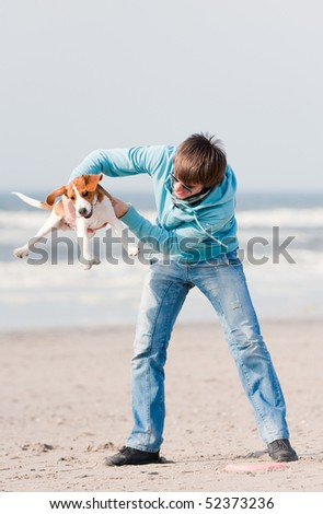 Young man playing with his beagle puppy - stock photo