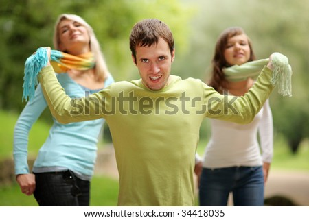 Young man playing with two girls. Shallow DOF. - stock photo