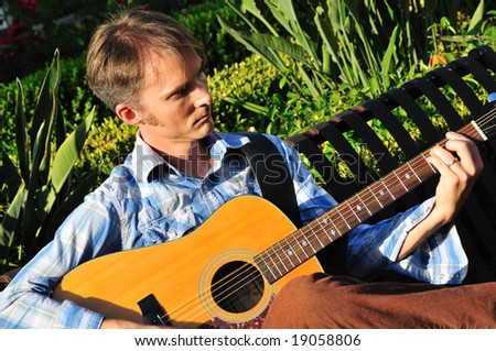 Young man plays guitar outside on a park bench - stock photo