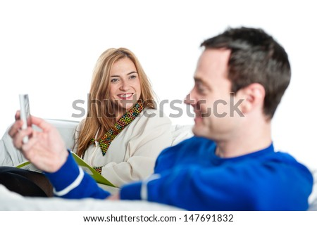 Young man plays on his phone and chats to his partner on the sofa - stock photo