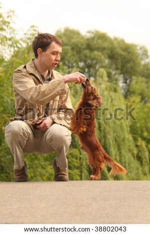Young man plays with his adorable dachshund  outdoor