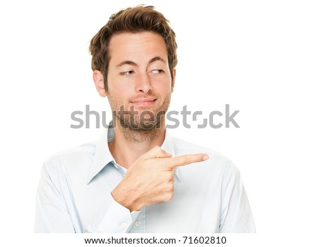 Young man pointing a bit sneaky looking at copy space. Handsome young Caucasian businessman isolated on white background. - stock photo