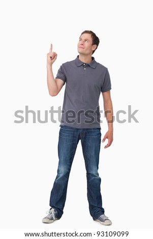 Young man pointing and looking up against a white background - stock photo