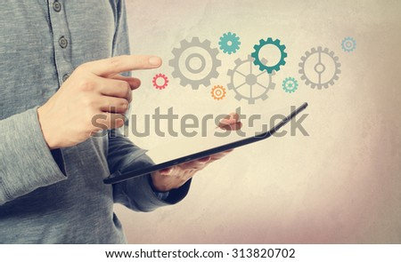 Young man pointing at colorful gears over a tablet computer - stock photo