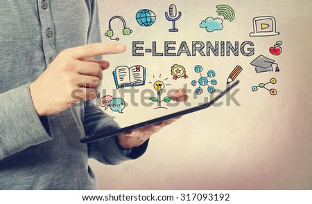 Young man pointing at E-Leaning concept over a tablet computer - stock photo
