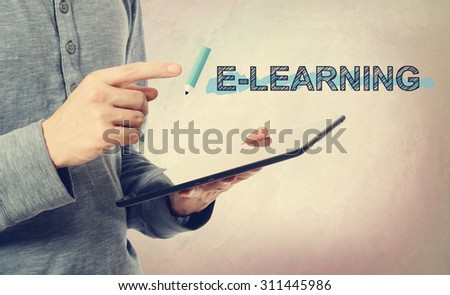 Young man pointing at E-Leaning text over a tablet computer - stock photo