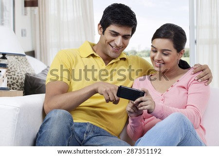Young man pointing at mobile phone while watching something with girlfriend - stock photo