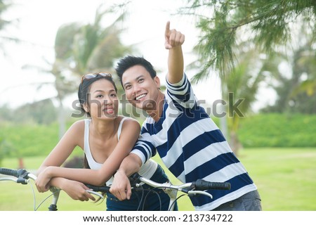 Young man pointing at something while standing in the park with his pretty girlfriend - stock photo