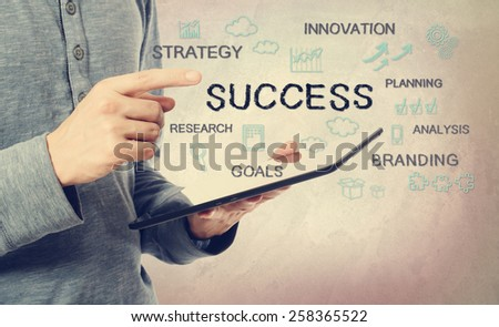 Young man pointing at success concepts over a tablet computer - stock photo