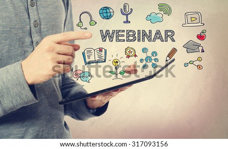 Young man pointing at Webinar concept over a tablet computer - stock photo