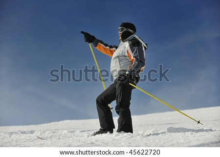 young man pointing direction on winter season during recreation ski on mountain with show - stock photo