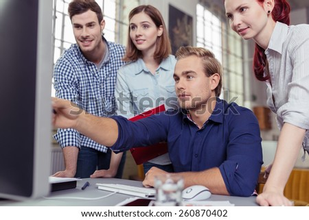 Young man pointing out something on his computer monitor to a group of young business colleagues in a teamwork and leadership concept