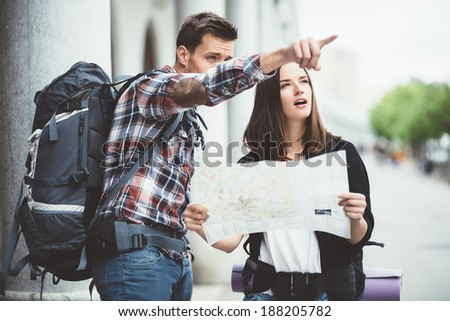 Young man pointing to a landmark backpackers in the city - stock photo